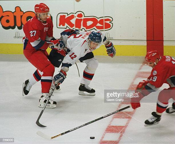 Peter Bondra of Slovakia is ridden off the puck by the defense of Alexai Kovalev and Alexei Yashin of Russia during the first period of their World...