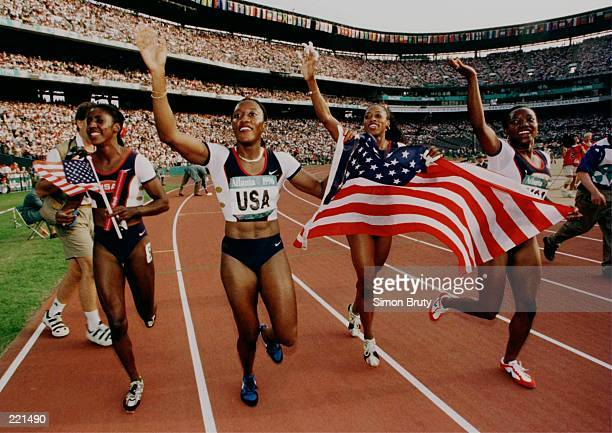 The USA 4x100 relay team Gwen Torrance Inger Miller Gail Devers and Christy Gains celebrate after winning the gold medal during the 1996 Centennial...