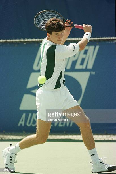 Tim Henman of Great Britain focuses on the ball as he sets his feet to attempt a back hand return during his match against Doug Flach of the USA in...