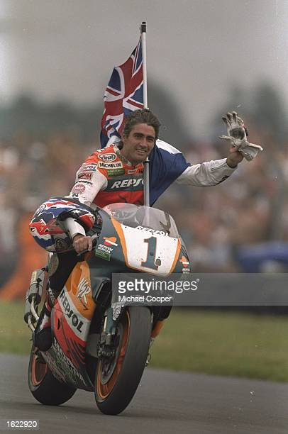 Michael Doohan of Australia celebrates his fourth successive world 500cc title at the British Motorcycle Grand Prix at Donington Park, England. \...
