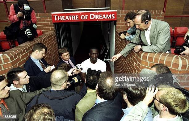 Dwight Yorke of Trinidad and Tobago in the media spotlight after completing his 12 million pound transfer to Manchester United at Old Trafford in...