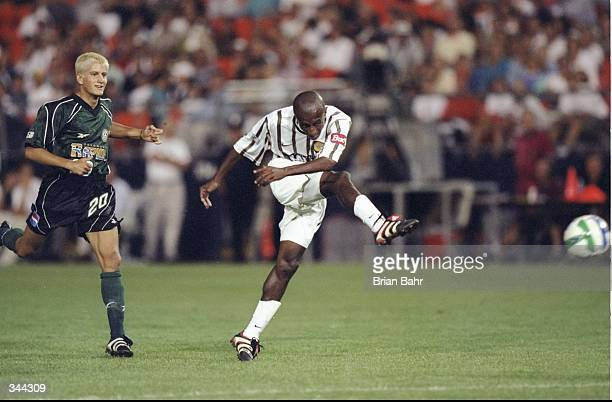 Ezra Hendrickson of the Los Angeles Galaxy shoots the ball as Ross Paule of the Colorado Rapids looks on during a game at the Mile High Stadium in...