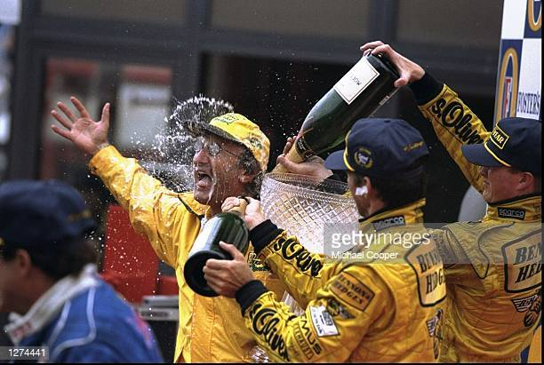 Jordan boss Eddie Jordan is sprayed with champagne by winner Damon Hill of Great Britain and Ralf Schumacher of Germany both of Jordan Mugen Honda at...
