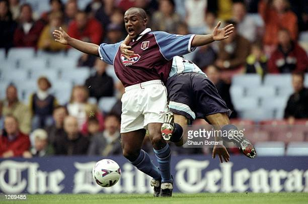 Julian Joachim of Aston Villa is held by Gianluca Festa of Middlesbrough during the FA Carling Premiership match at Villa Park in Birmingham England...