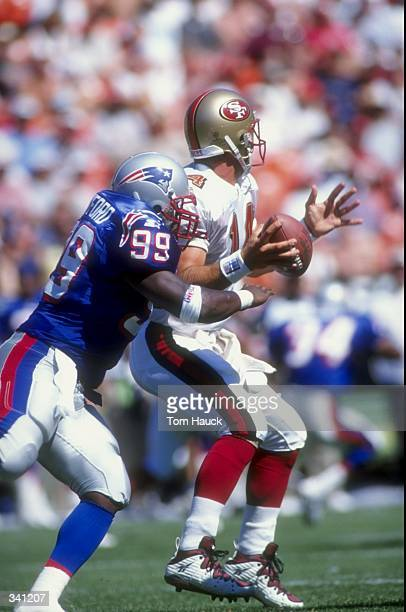 Linebacker Vernon Crawford of the New England Patriots tackles quarterback Jim Druckenmiller of the San Francisco 49ers during a preseason game at...