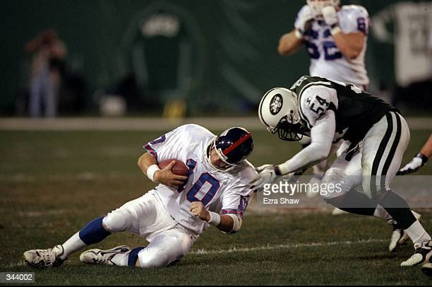 Quarterback Kent Graham of the New York Giants in action against linebacker Dwayne Gordon of the New York Jets during an NFL preseason game at the...