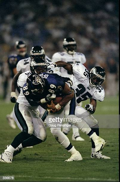 Safety Anthony Marshall and line backer Mike Caldwell of the Philadelphia Eagles tackle AJ Ofodile of the Baltimore Ravens during a preseason game at...