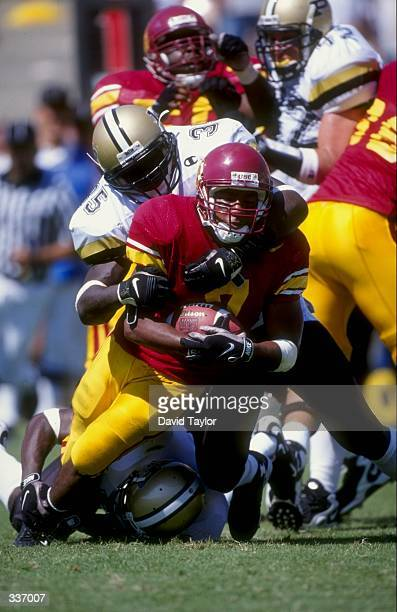 Tailback Chad Morton of the USC Trojans grips the ball as he is tackled during the Pigskin Classic game against the Purdue Boilermakers at Los...