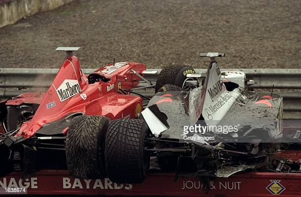 The Ferrari of Eddie Irvine and the Maclaren Mercedes of David Coulthard loaded on a recovery vehicle after a crash at the first corner of the...