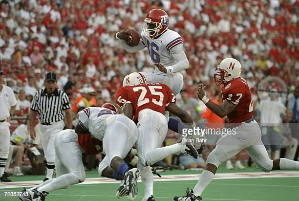 Troy Edwards of the Louisiana Tech Bulldogs is tackled in the air by Joe Walker of the Nebraska Cornhuskers during the Eddie Robinson Classic at Tom...