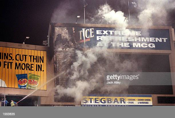 A Melbourne Cricket Ground official uses a fire hose to douse flames as a fire breaks out in the main scoreboard at The Melbourne Cricket Ground...