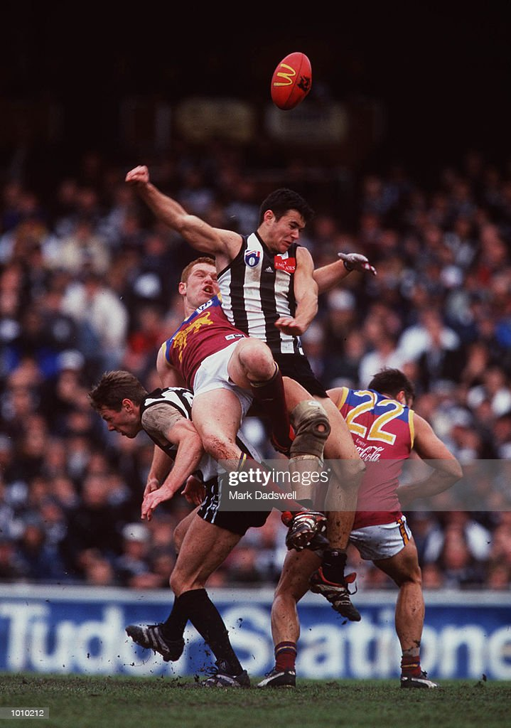 Chris Tarrant # 20 for Collingwood punches the ball clear as he lands on top of Justin Leppitsch # 23 for Brisbane during the AFL round 22 game Collingwood v Brisbane at Victoria Park Collingwood,Victoria,Australia.Brisbane defeated Collingwood. Mandatory Credit: Mark Dadswell/ALLSPORT