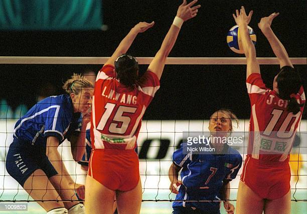 Elisa Togut of Italy on left spikes as Maurizia Cacciatori looks on and Lina Wang on left and Jing Chen of China try to defend during the first round...