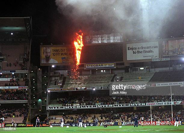 Fire destroys the main MCG scoreboard as players and officials warm up on the ground before the round 22 AFL game between Richmond and Carlton...