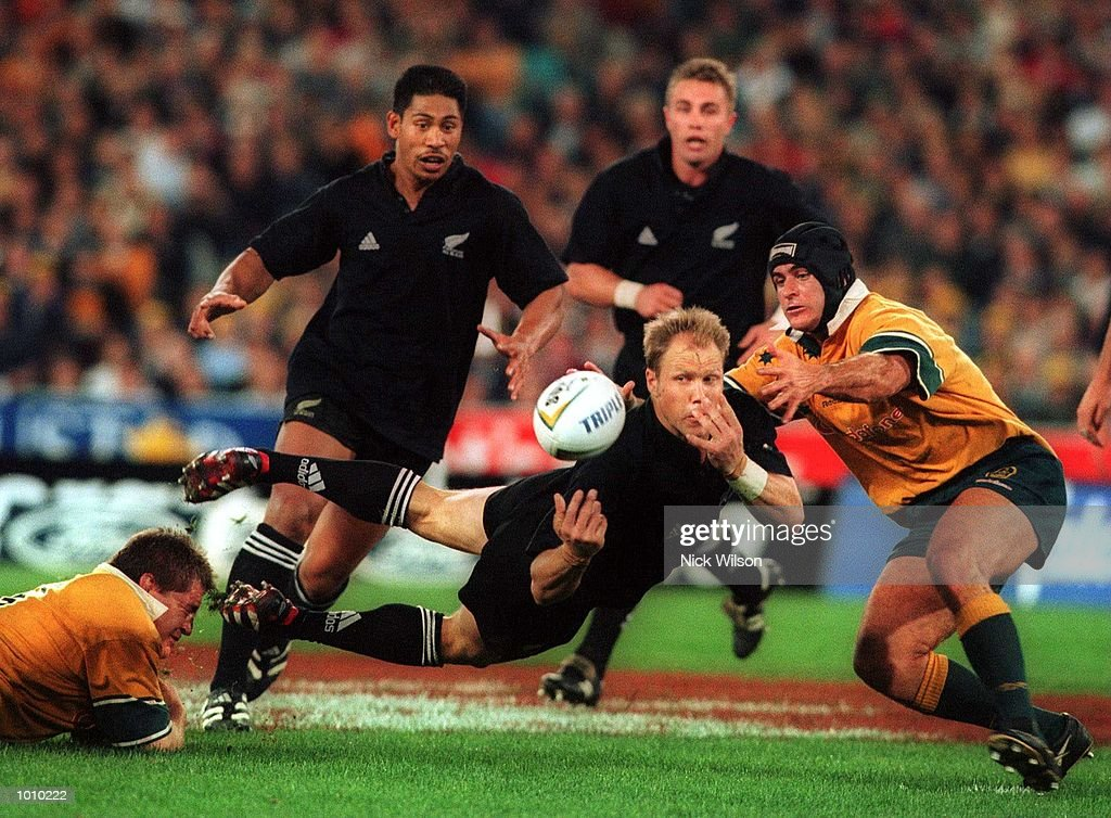 Jeff Wilson of New Zealand releases a pass despite the attentions of Australian captain David Wilson on the right during the Bledisloe Cup game at Stadium Australia, Homebush, Sydney, Australia. Australia won 28-7. Mandatory Credit: Nick Wilson/ALLSPORT