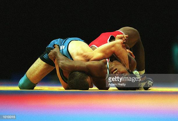 K Uresi of Solomon Islands in red backslams M Berberyan of Armenia in the blue in the freestyle 58kg class during the Fila junior world freestyle...