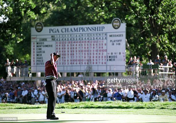 Tiger Woods celebrates as he makes the winning putt during the PGA Championships at the Medinah Country Club in Medinah Illinois Mandatory Credit...