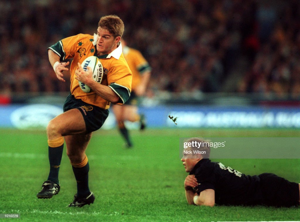 Tim Horan of Australia evades the tackle of Jeff Wilson of New Zealand in front of a new world record crowd of 108,000 for a rugby union international during the Bledisloe Cup game between Australia and New Zealand at Stadium Australia, Homebush, Sydney, Australia. Australia won 28-7. Mandatory Credit: Nick Wilson/ALLSPORT