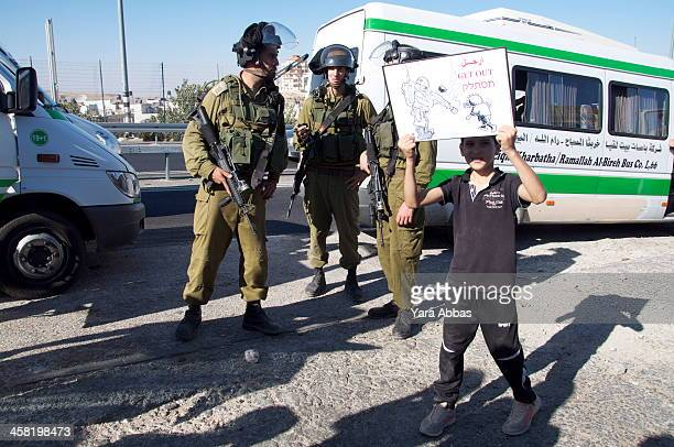 Aug 1st 2013 - Protest against prawer plan in Hizma Palestinian Child in Hizme near Jerusalem holds a poster infront of Israeli Occupation Forces in...