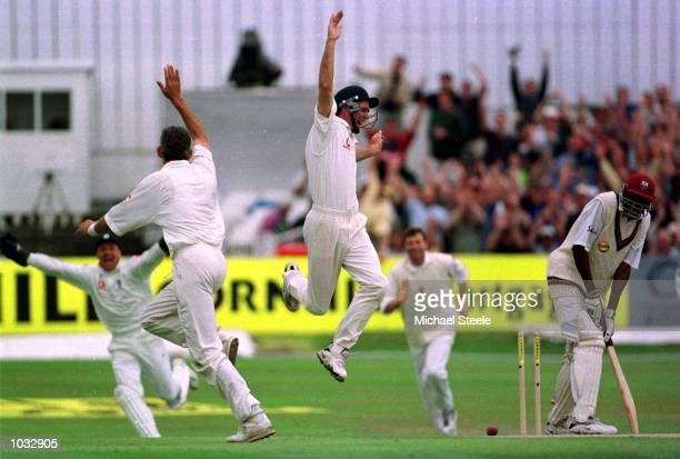 Andy Caddick and Michael Vaughan of England celebrate the wicket of Curtly Ambrose of the West Indies during the second day of the England v West...