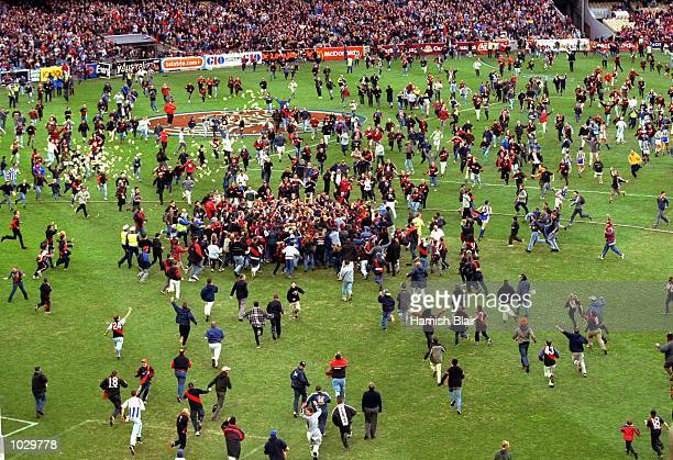 Crowd stream onto the ground after Matthew Lloyd for Essendon kicked his 100th goal for the season in the AFL 1st Qualifying Final match between the...