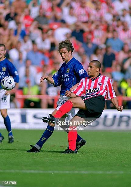 Curtis Woodhouse of Sheffield United shoots past Thomas Thorgensen of Portsmouth during the Nationwide League Division One match at Bramall Lane in...