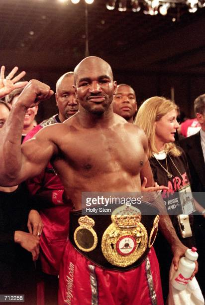 Evander Holyfield celebrates in the ring as he wears the Heavyweight belt after a WBA Heavyweight Championship fight against John Ruiz at the Paris...