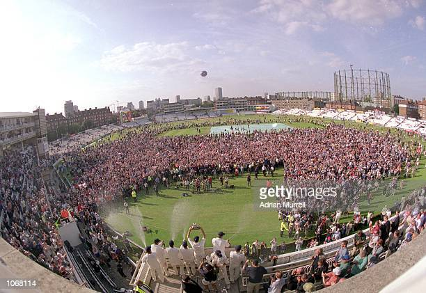 Fans congregate on the pitch to celebrate after the fifth Test match between England and the West Indies at The Oval in London England won the match...