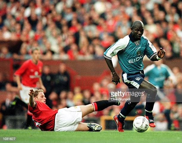 George Weah of Man City avoids the tackle of Nicky Butt of Man Utd during the Manchester United v Manchester City Denis Irwin Testimonial match at...