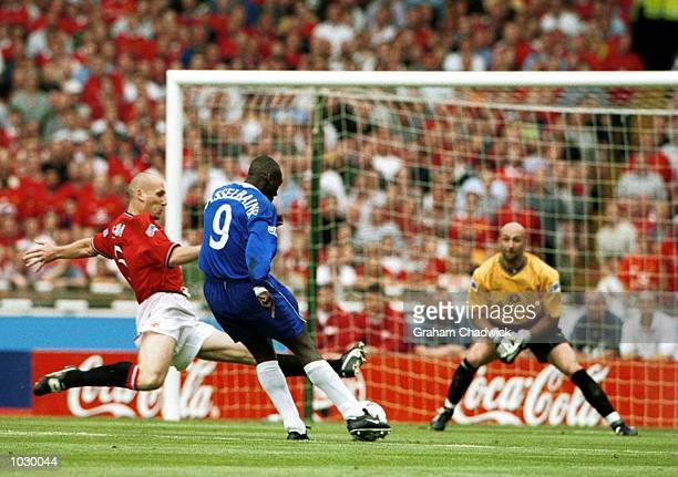 Jimmy Floyd HasselBaink of Chelsea shots to score the opening goal under pressure from Jaap Stam of Manchester United during the match between...