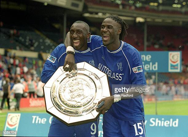 Jimmy Hasselbaink and Mario Melchiot of Chelsea lift the trophy after winning the One 2 One FA Charity Shield match against Manchester United at...