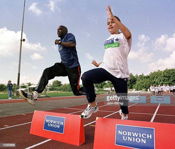 Mark Richardson races with kids over the hurdles during the Norwich Union Startrack at Coventry Athletic Track at Warwick University Coventry...
