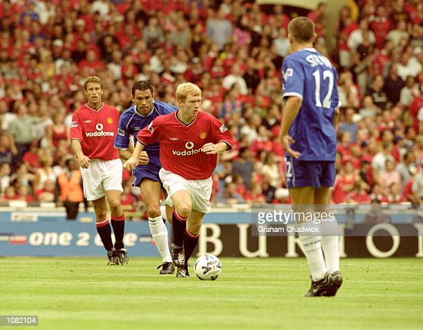 Paul Scholes of Manchester United is chased by Gustavo Poyet of Chelsea during the Charity Shield match played at Wembley Stadium in London Chelsea...