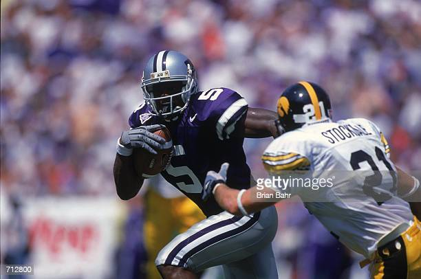 Quincy Morgan of the Kansas State Wildcats runs with the ball as Matt Stockdale of the Iowa Hawkeyes comes at him during the Eddie Robinson Classic...