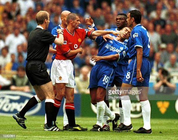 Referee MRiley steps in to stop a tussel between Roy Keane of Manchester United and Roberto Di Matteo of Chelsea before giving Roy Keane a red card...
