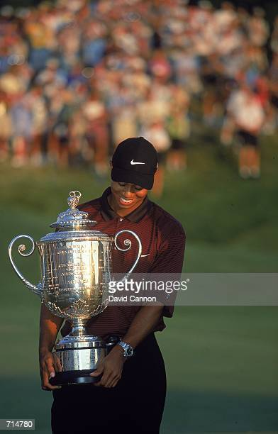 Tiger Woods reacts to winning while holding his trophy after the PGA Championship part of the PGA Tour at the Valhalla Golf Club in Louisville...