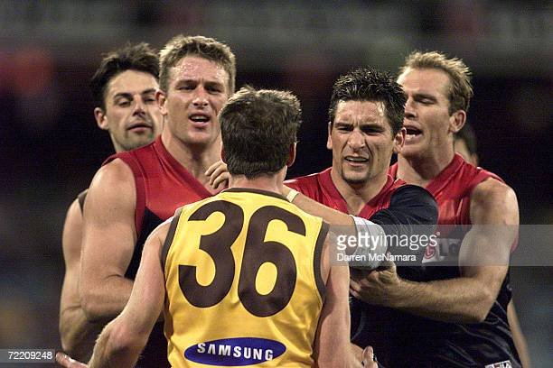 David Schwarz and Adem Yze for Melbourne argue with Matthew Dent for Hawthorn during the AFL round 19 game between the Melbourne Demons and the...