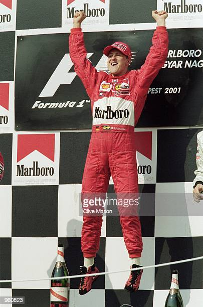 Ferrari driver Michael Schumacher celebrates on the podium after winning the Formula One Hungarian Grand Prix to secure his fourth World Championship...