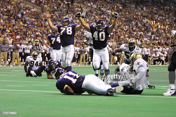 Jim Kleinsasser of the Minnesota Vikings and teammates throw up their arms in celebration over a scoring run by Daunte Culpepper against the New...