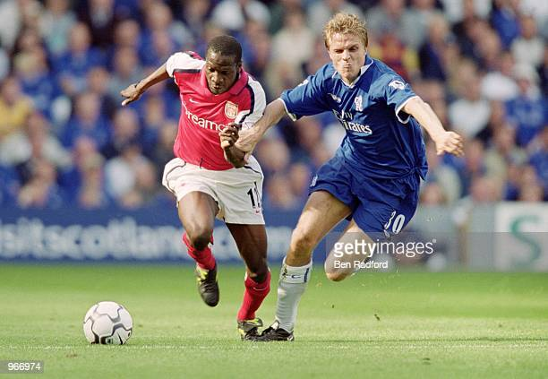 Lauren of Arsenal battles with Jesper Gronkjaer of Chelsea during the FA Barclaycard Premiership match played at Stamford Bridge in London The game...