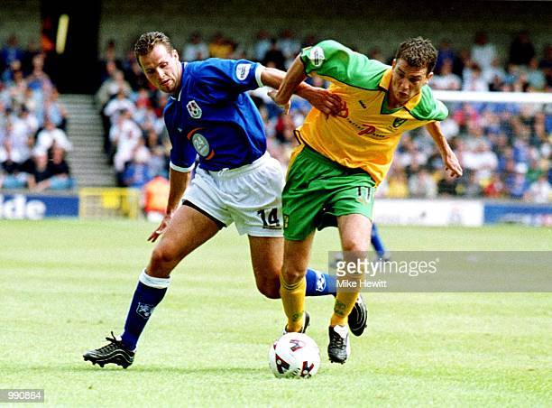 Lucas Neill of Millwall tries to tackle Chris Llewellyn of Norwich City during the Nationwide Division One match between Millwall and Norwich City at...