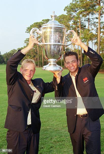 Luke Donald and Nick Dougherty of Great Britain and Ireland hold the trophy aloft after the 38th Walker Cup match played at the Ocean Forest Golf...