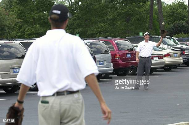 Phil Mickelson tosses the ball with his caddie Jim 'Bones' MacKay before teeing off during the final round of the 83rd PGA Championship at Atlanta...