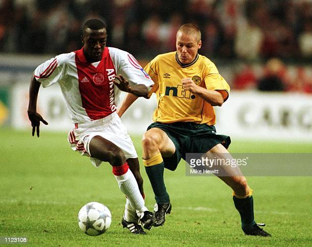 Steve Guppy of Celtic tries to tackle Yakubu Abubakari of Ajax during the UEFA Champions League Third Qualifying Round First Leg match between Ajax...