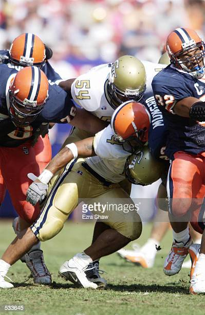 Tailback James Mungro of Syracuse is hit by strong safety Cory Collins and linebacker Keyaron Fox of Georgia Tech during the Kickoff Classic at...