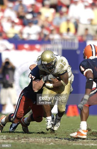 Tailback Joe Burns of Georgia Tech tries to avoid being tackled by defensive end Josh Thomas and safety Cory Collins of Syracuse during the Kickoff...
