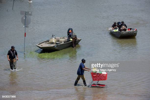 Aug 31 2017 A man walks by rescuers on a flooded road in Port Arthur Texas the United States Aug 31 2017 Nearly 40 people died or are feared dead in...