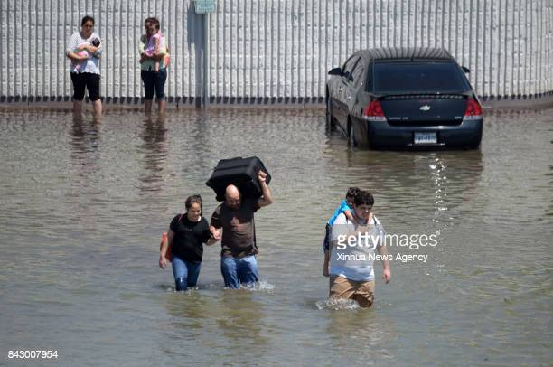 Aug 31 2017 Residents walk on a flooded road when leaving their neibourhood in Port Arthur Texas the United States Aug 31 2017 Nearly 40 people died...