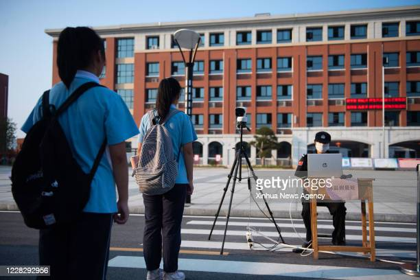 Aug. 31, 2020 -- Students have their temperature measured at Daowu middle school in Liuyang City of Changsha, capital of central China's Hunan...
