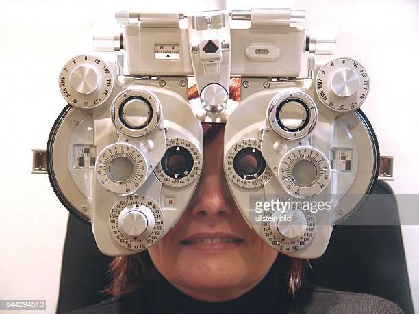 Augenarzt Augenkrankheiten Sehschwaeche Patientin beim Augenarzt Optiker mit Geraet zum Anpassen einer Brille